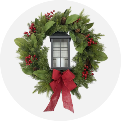 A Christmas wreath with a red bow around an outdoor light.